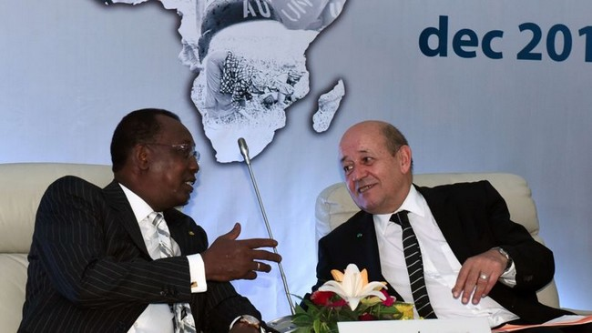 "French Defence Minister Jean-Yves Le Drian (R) speaks to Chadian President Idriss Deby Itno as they attend the last day of the International Forum on Peace and Security in Africa in Dakar on December 16, 2014. Malian President Ibrahim Boubacar Keita called on the world community to put an end to instability in southern Libya, which he called a ""hornet's nest"" and a ""fabulous market of weapons to our countries."" AFP PHOTO / SEYLLOU"